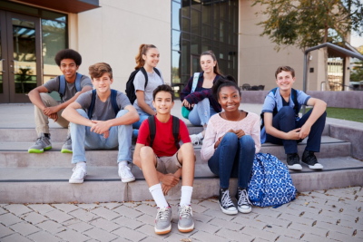Portrait Of High School Student Group Sitting Outside College Buildings