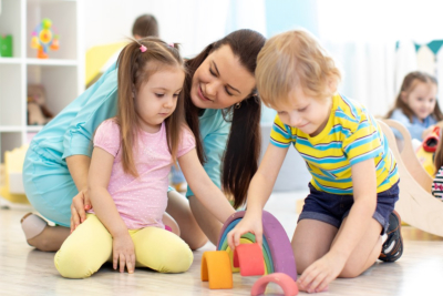 Preschool children and kindergarten teacher playing with wooden toys
