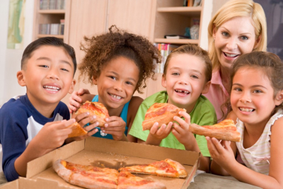 Four young children indoors with woman eating pizza