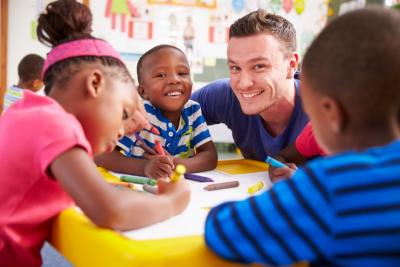 Volunteer teacher helping a class of preschool kids drawin