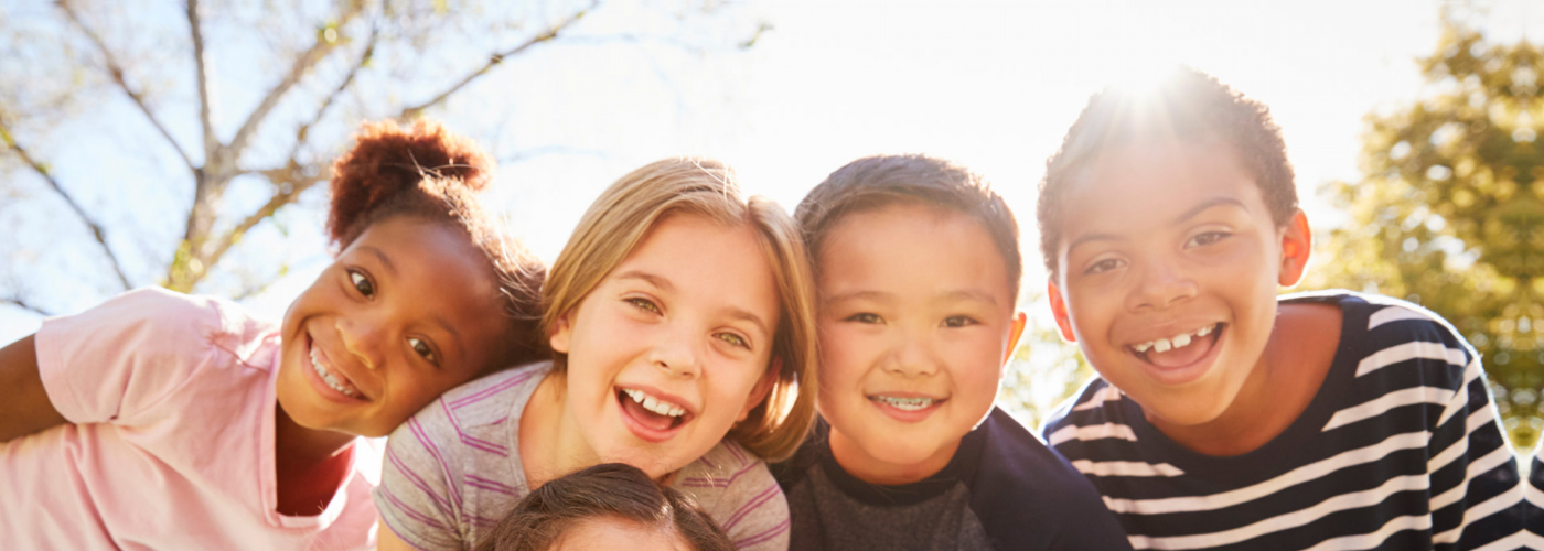 Multi-ethnic group of schoolchildren on school trip, smiling