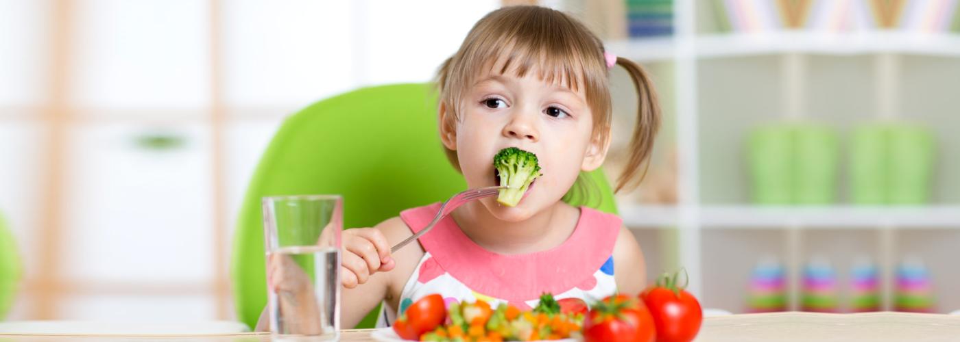 Child little girl eats vegetable salad using fork
