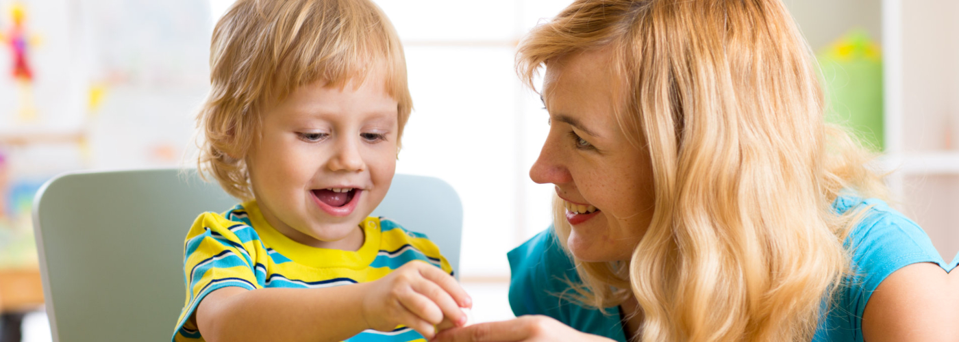 Woman and child boy talking and smiling while playing